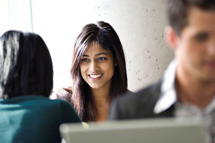 Junge Geschäftsfrau spricht mit einer Kollegin.